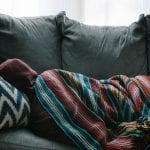 person on couch as COVID-19 symptoms linger